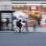 man cycling through urban street