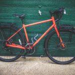 Orange touring bike against green wall