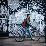 man walking in street with bicycle and graffiti behind him
