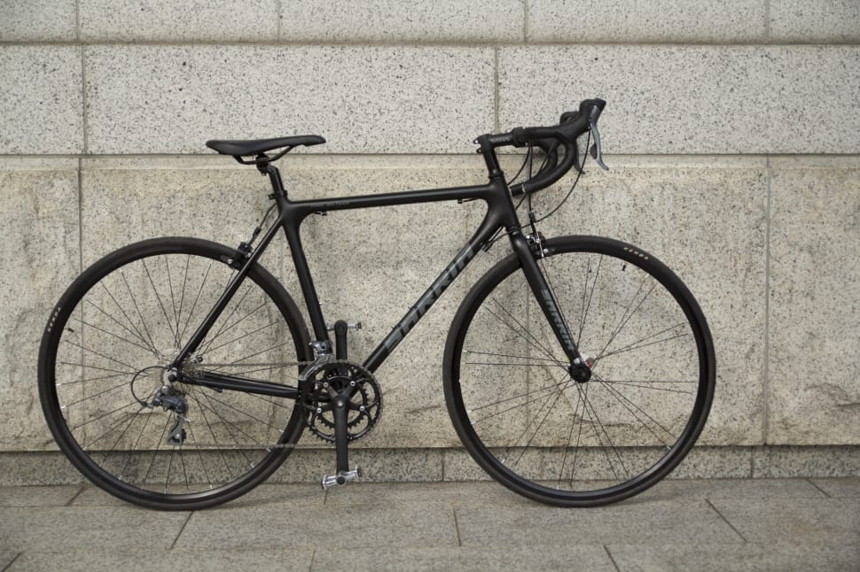 a road bike with handlebars propped up against a wall to demonstrate their design for beginner commuters