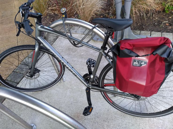 silver hybrid bike locked up with 2 red pannier bags on the back