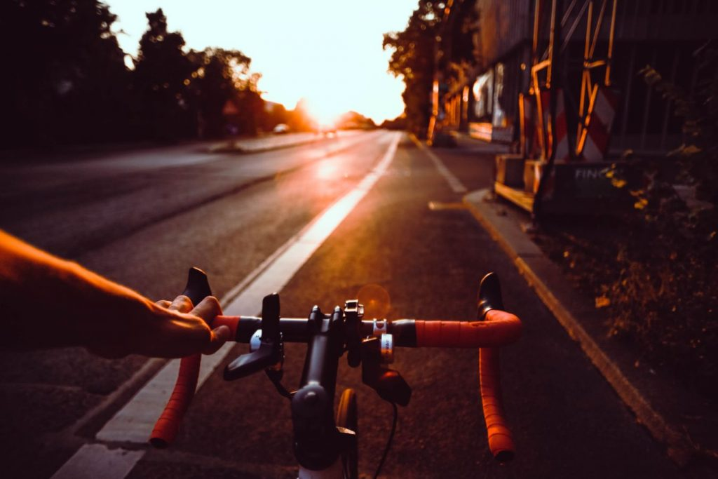 riding drop handlebar bike on road with sunset