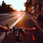 riding drop handlebar bike on road with sunset