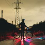 man standing in the street with bike and with bright colored lights