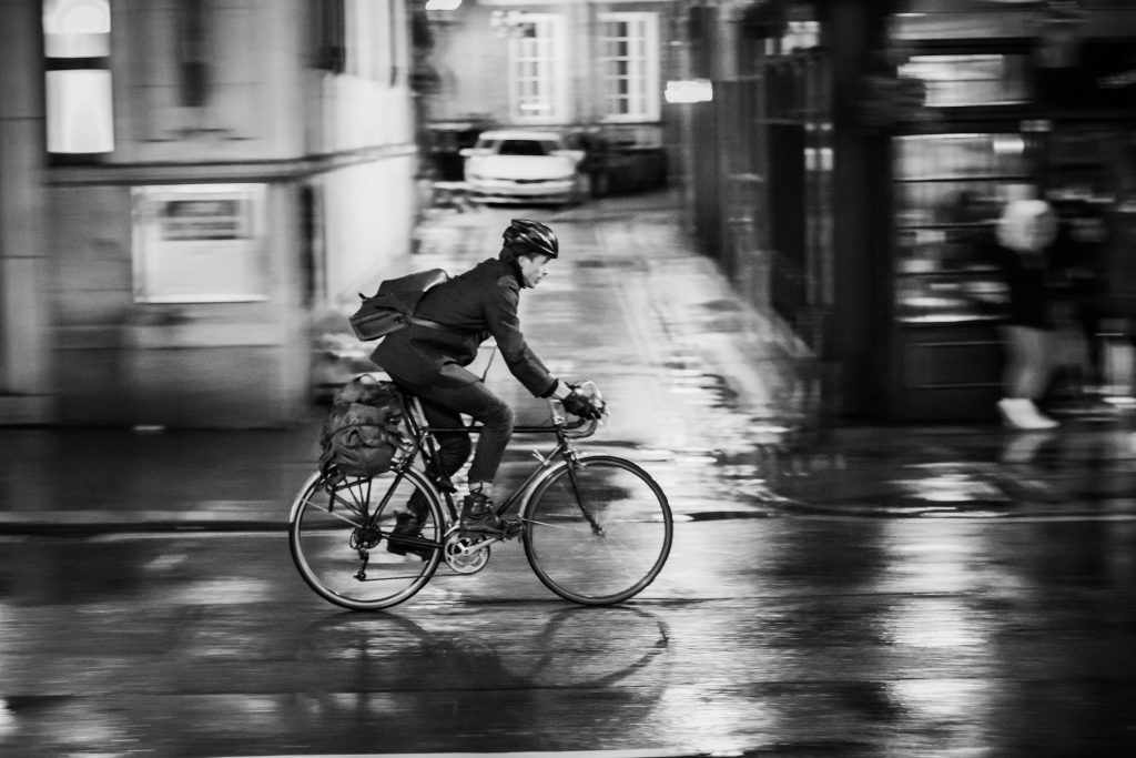 man cycling through the street in the rain in formal work clothes and waterproof clothing